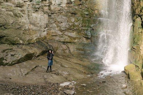 Woman in Black Jacket Standing on Rock Near Waterfalls