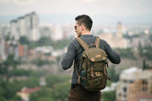 Man in Gray Long Sleeve Shirt Carrying Brown Backpack