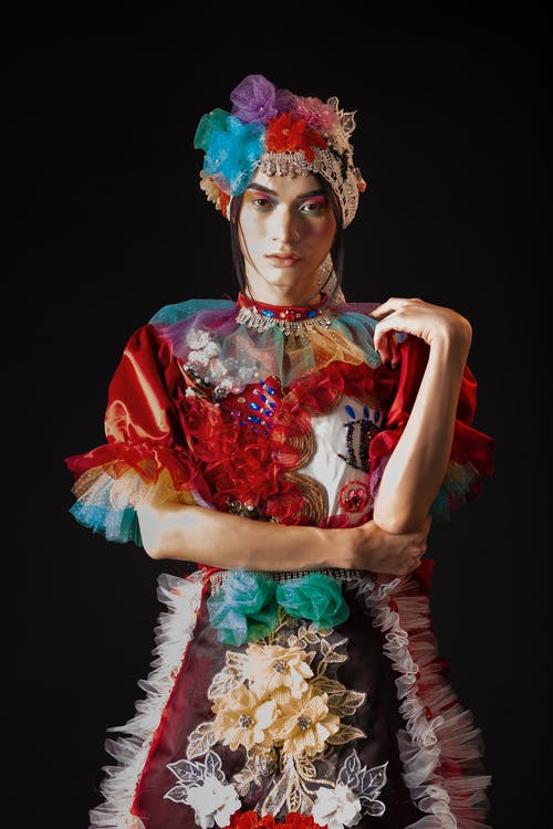 Artistic female in retro costume with floral headdress standing on black background with hand on elbow and looking at camera