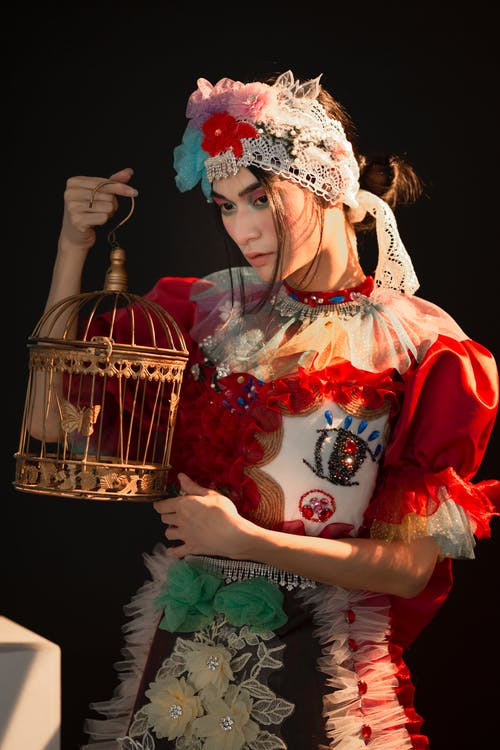 Charming lady wearing eccentric decorated headgear standing against black background with decorative golden cage in hands while looking away in studio