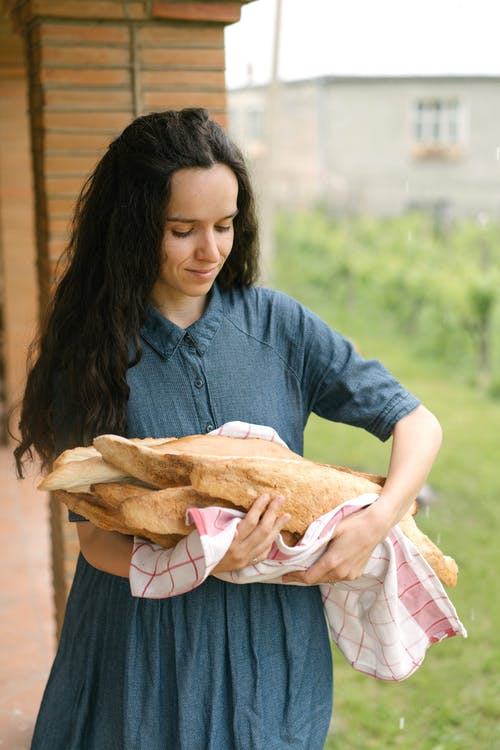 Photo of Woman in Blue Dress Holding Baguette