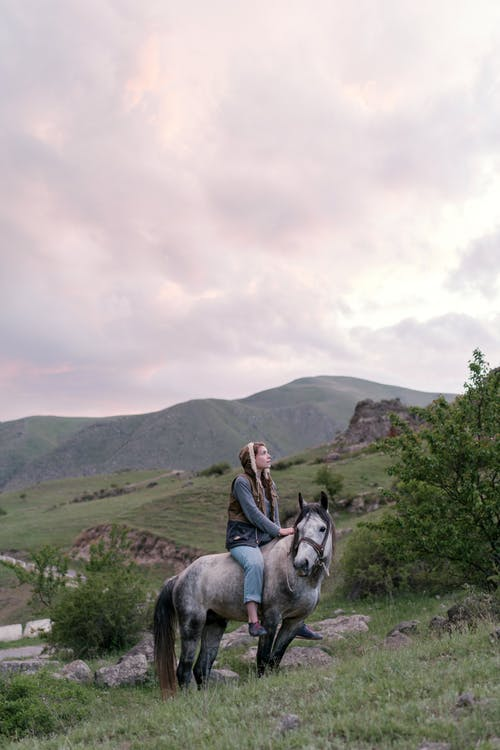 Person Riding White Horse Under Cloudy Sky