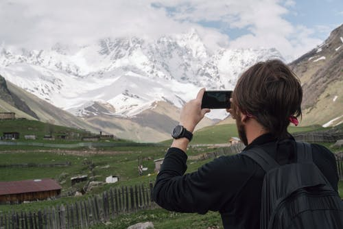Man in Black Jacket Taking Photo of White Clouds and Snowy Mountain