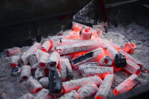 Small hexagonal coals with holes smoldering on metal rack before roasting barbecue in nature