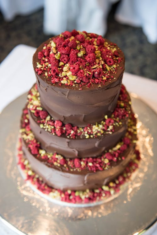 From above yummy tiered chocolate cake decorated with ripe raspberries and nuts served on table