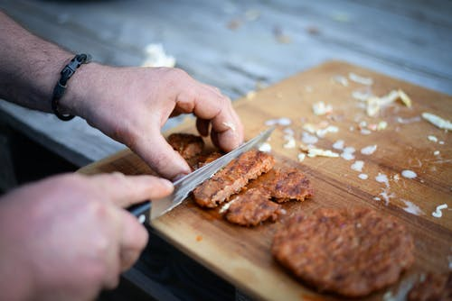 Crop anonymous male cook cutting yummy grilled cutlet on wooden board before serving