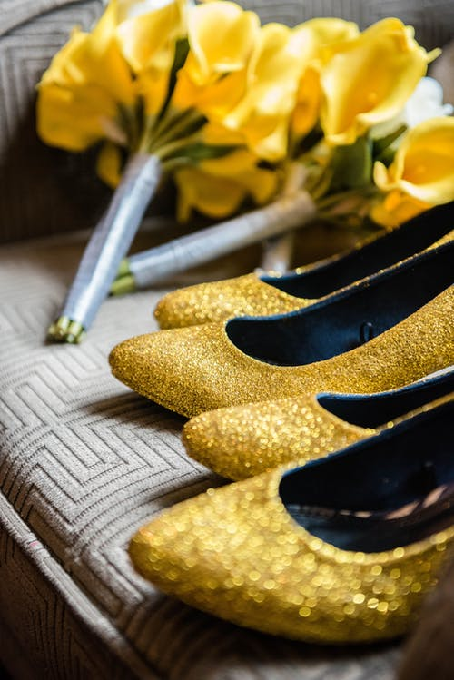 Stylish golden shoes and yellow bouquets on sofa