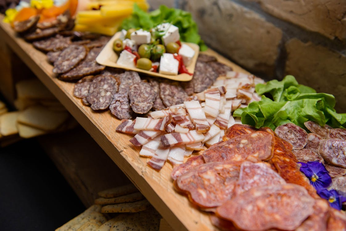 High angle appetizing sliced cured pork fat and smoked sausages served on sideboard with cheese and olives during buffet catering