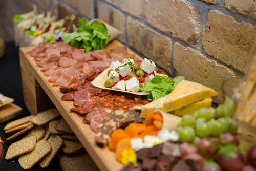 Buffet with various sausages and cheese on sideboard