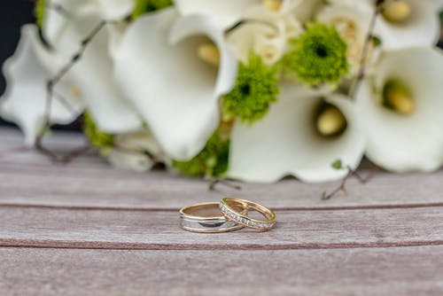 Wedding rings on wooden surface against bouquet of white flowers