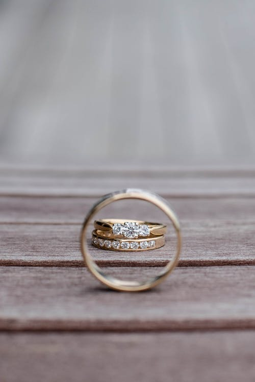 Composition of elegant wedding rings with diamonds on wooden surface