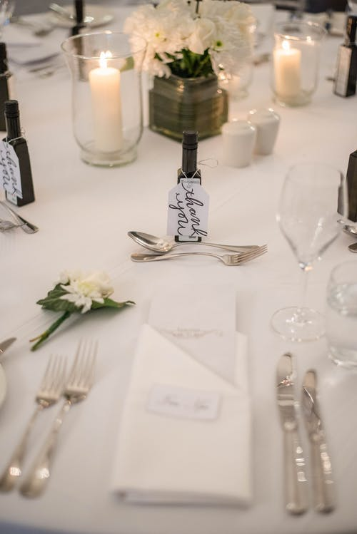 High angle composition of exquisite table setting with silverware and wineglasses served on white tablecloth decorated with burning candles and tender white flowers