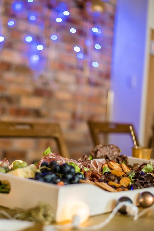 Tasty various appetizers arranged on banquet table in modern restaurant against wall decorated with shining garlands