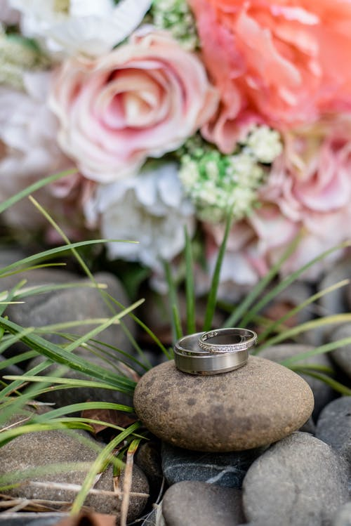 Bright flower bouquet near rings on stones