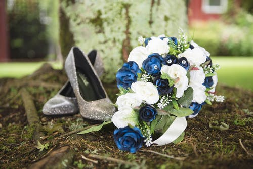 Colorful bridal bouquet near pair of shoes in summer