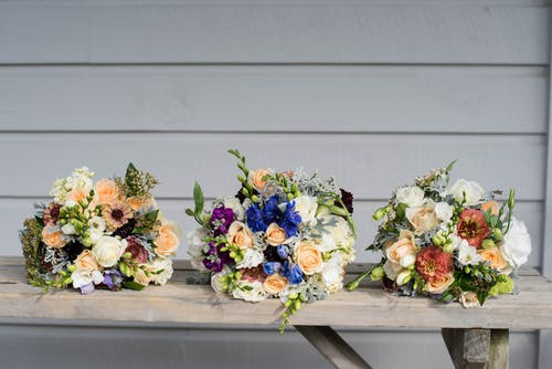 Composition of bright blooming flower bouquets on wooden table near wall on wedding day