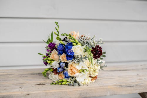 Bright blossoming flower bouquet with roses on table near wall during festive event
