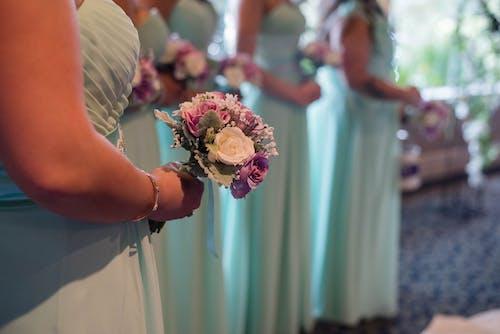 Crop elegant bridesmaids with flower bouquets on wedding ceremony