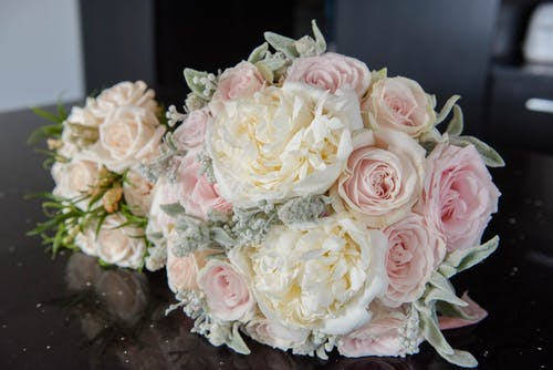 Rose buds with gentle petals in colorful bridal bouquets on black table during festive event