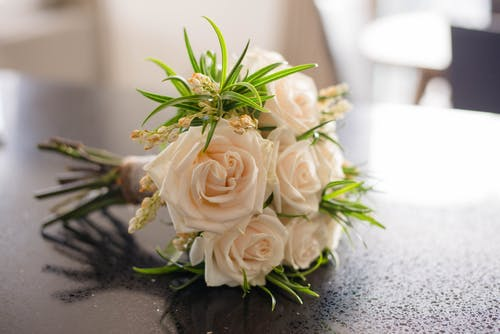 Colorful bridal bouquet with leaves on table
