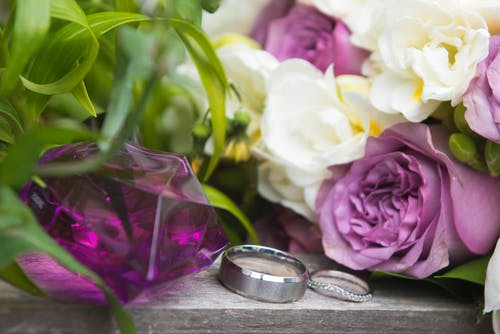 Silver rings near bright blossoming flowers on wedding day