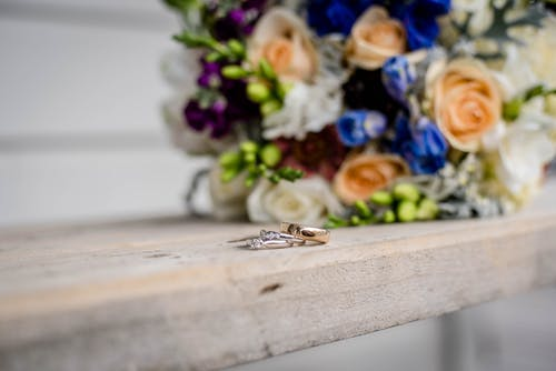 Shiny rings with precious stones near bright blossoming flower bouquet on wooden surface on wedding day