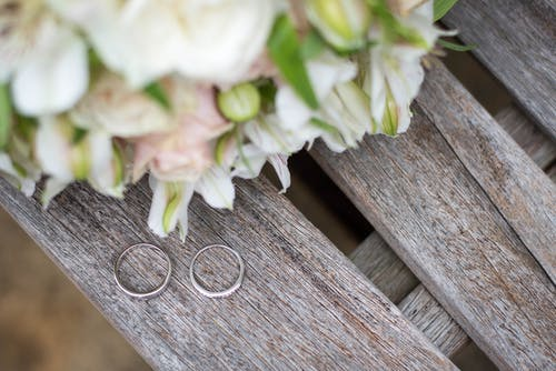 Rings near bright bridal bouquet on wooden surface