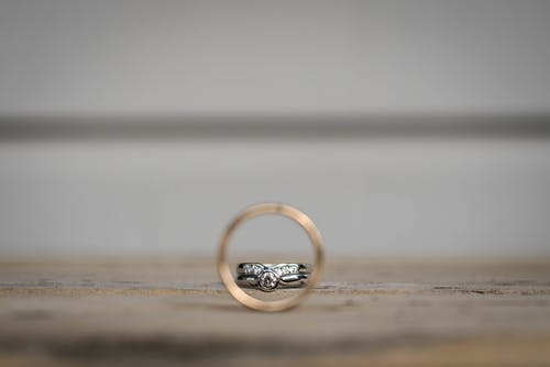 Closeup of golden and silver rings with precious stones on shabby surface on wedding day