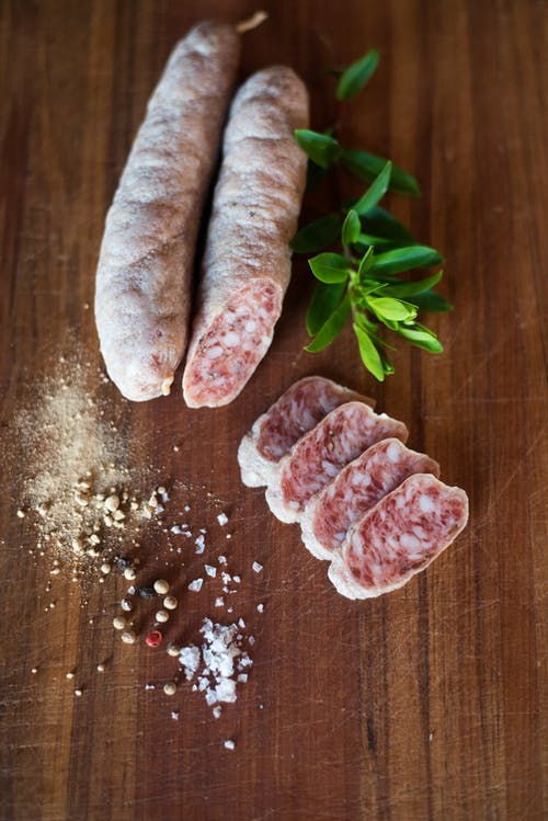Yummy salami slices with seasonings on table
