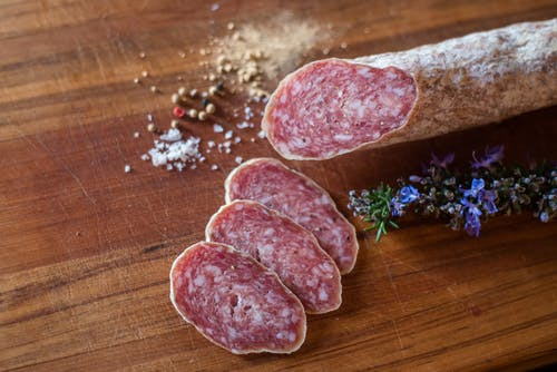 Delicious salami slices near spices and rosemary