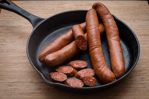 Tasty sausages in frying pan on table