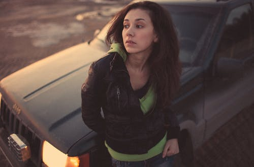 Woman in Black Leather Jacket Standing Beside Black Car