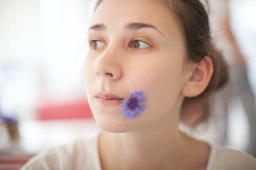 Portrait Photo of Woman Biting Blue Flower