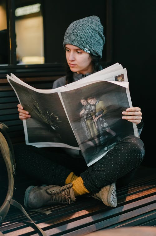 Photo of Woman Sitting While Reading Newspaper