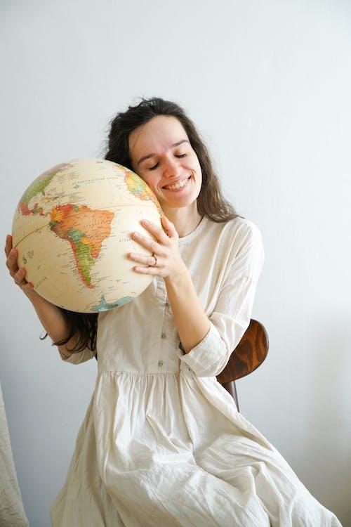 Woman in White Dress Holding Globe