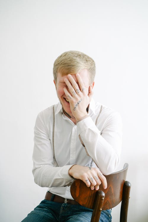 Man in White Dress Shirt Covering His Face With His Hand