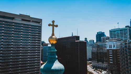 Golden cross on Christian church located in modern city