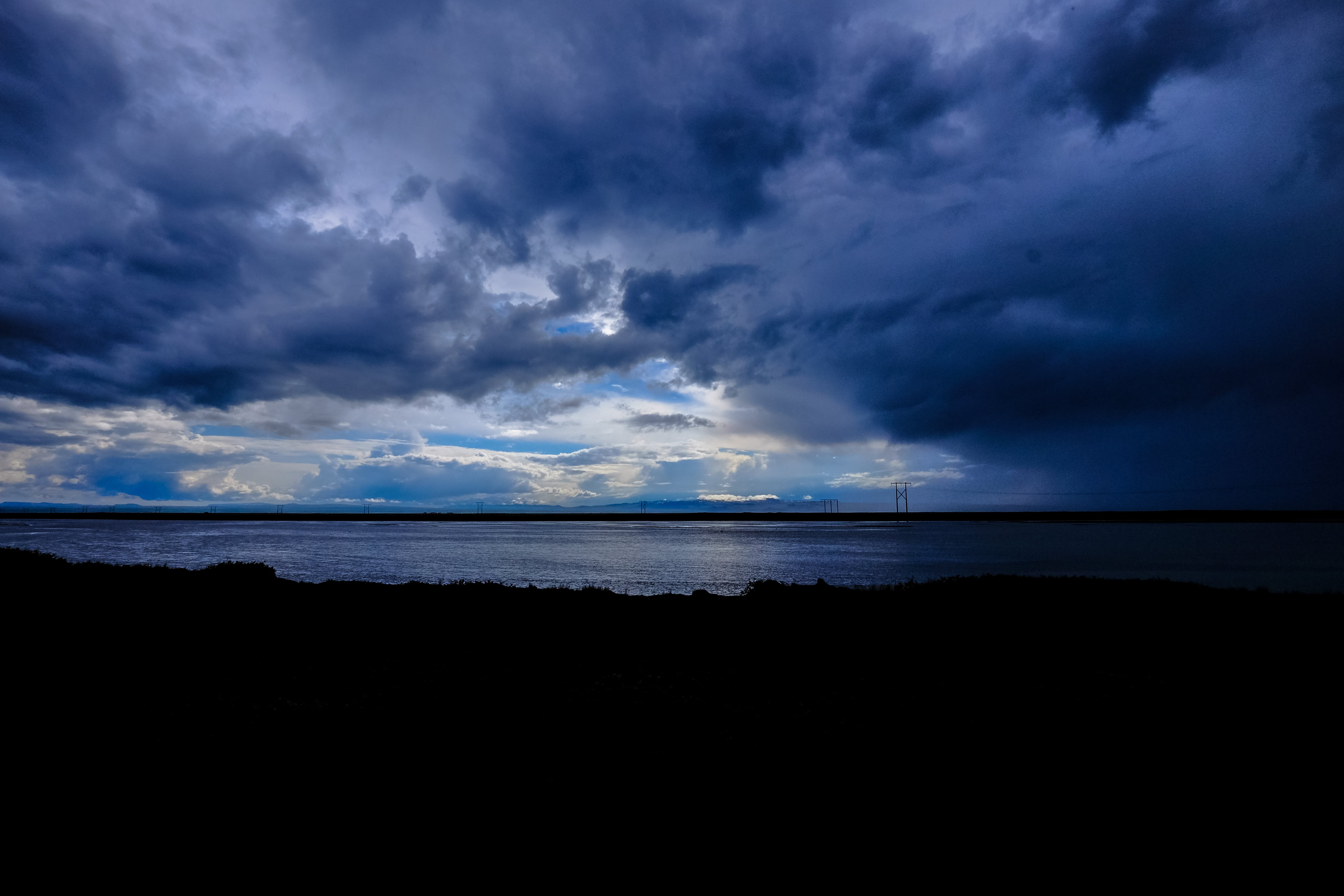 Silhouette Photo of Body of Water Under Thick Gray Clouds