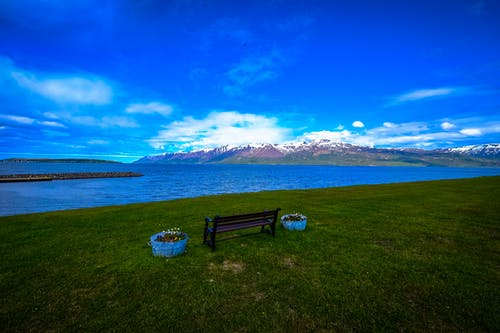 Black Bench Near Blue Ocean Under Blue Sky