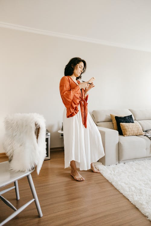 Stylish woman surfing internet on smartphone in living room