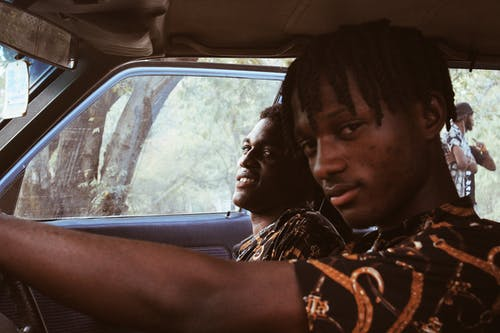 Black men sitting in car and looking at camera