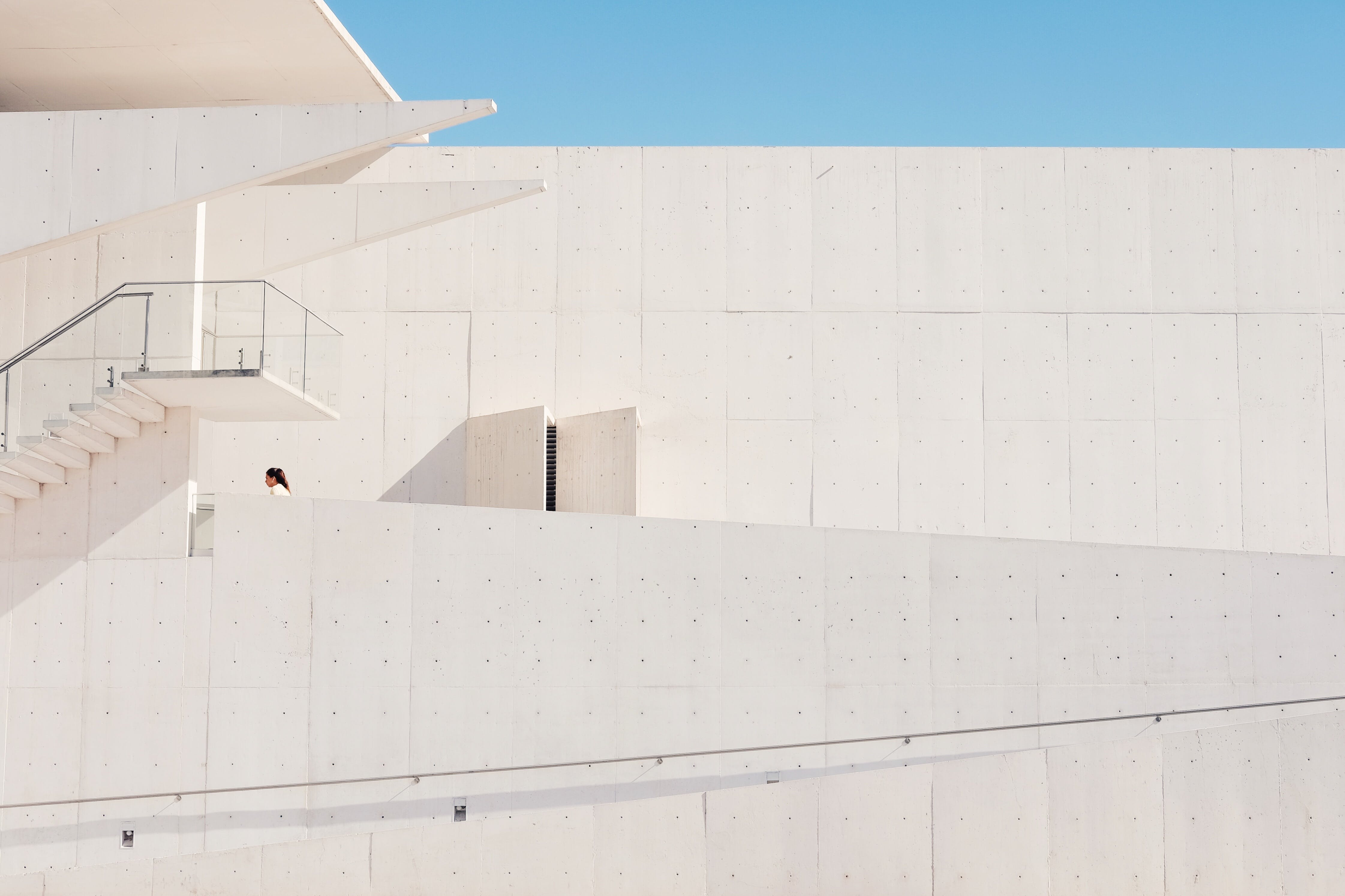 Person in White Shirt Walking on Concrete Building Under Blue Sky during Daytime