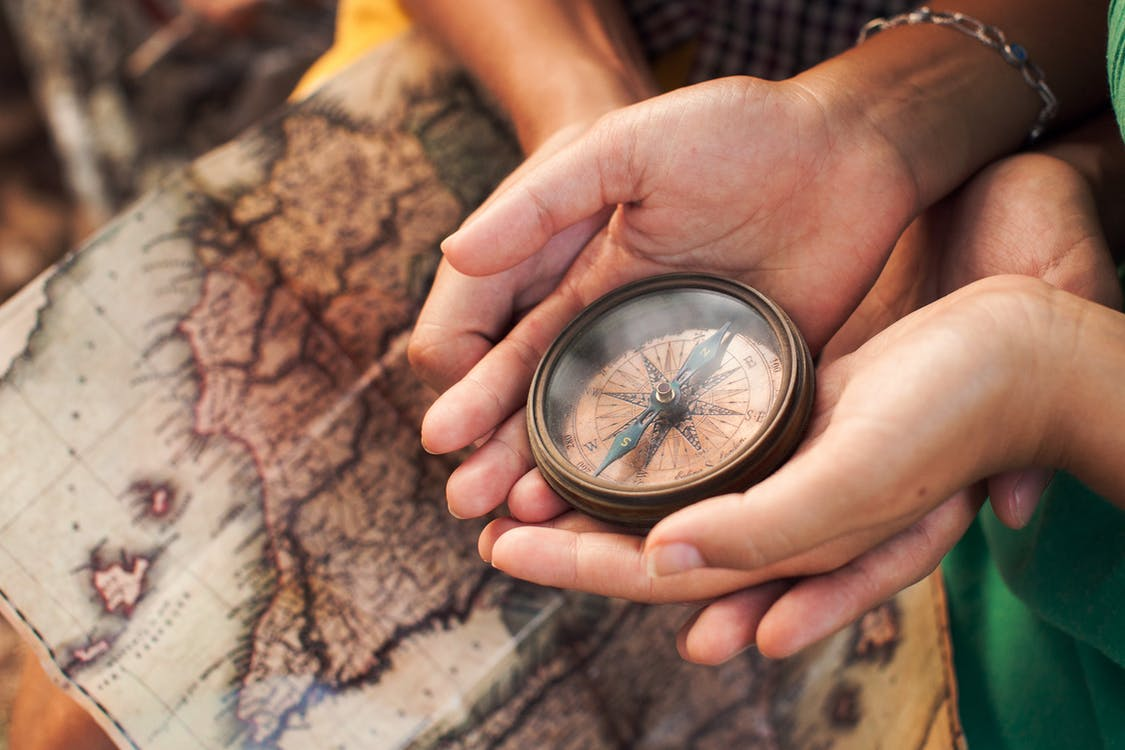 Person Holding Silver Round Compass