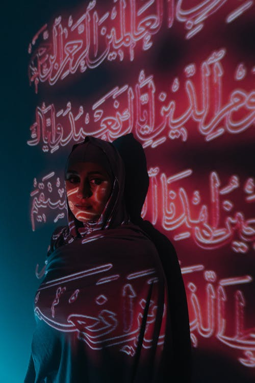Woman in Black Hijab and Black and Pink Hoodie