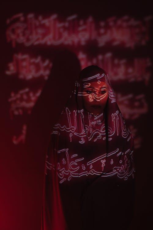 женщина в черном хиджабе и красно белом хиджабе