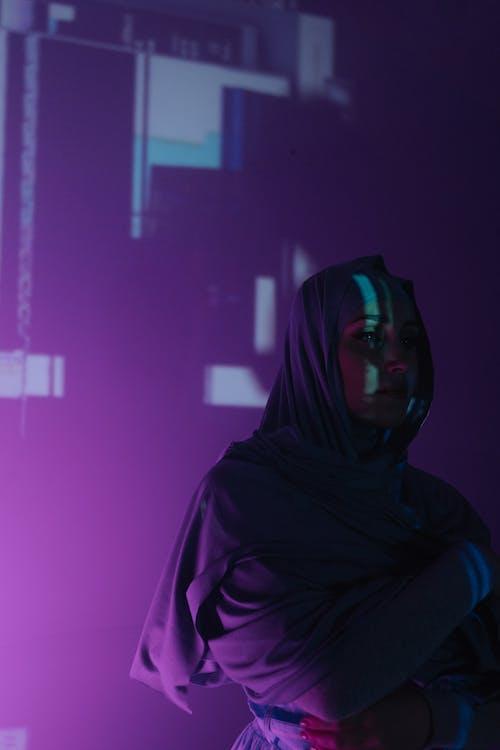 Woman in Black Hijab Standing Near Purple Wall