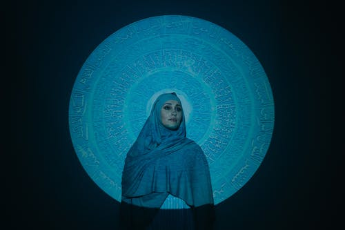 Woman in Blue Hijab Standing Beside Blue and White Wall