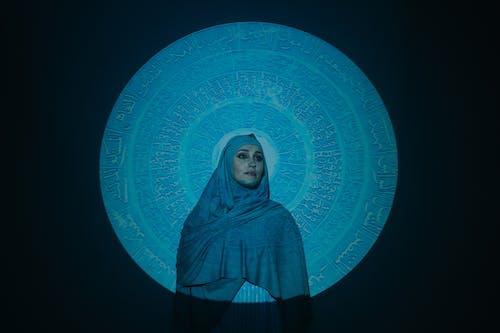 青と白の壁の横に立っている青いヒジャーブの女性