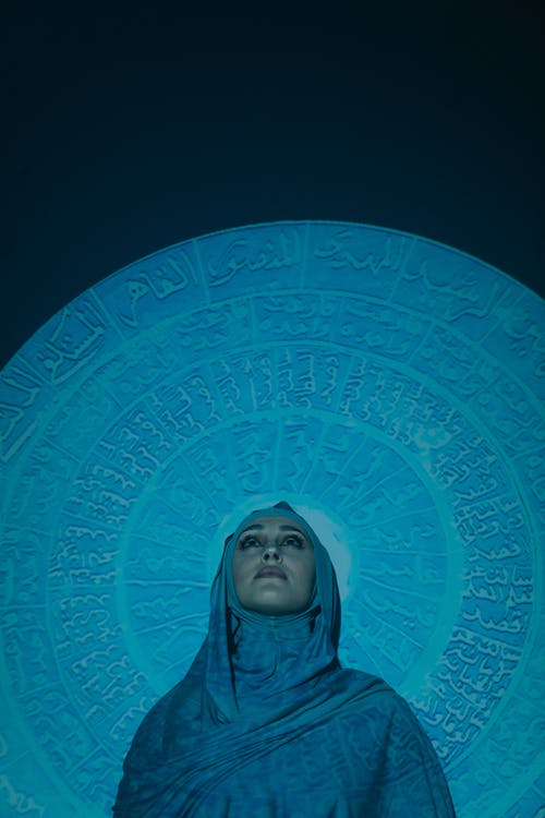 Woman in Gray Hijab on Blue Round Textile
