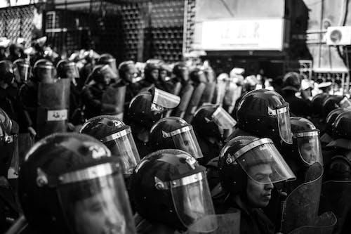 Grayscale Photo of People in Helmet